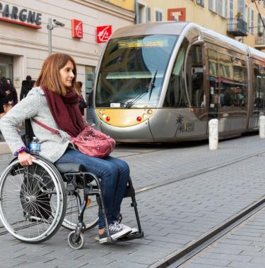 Femme en fauteuil roulant traverse une voie de tram.