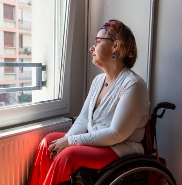 Personne en situation de handicap qui regarde par la fenêtre, en confinement, en isolement chez elle.